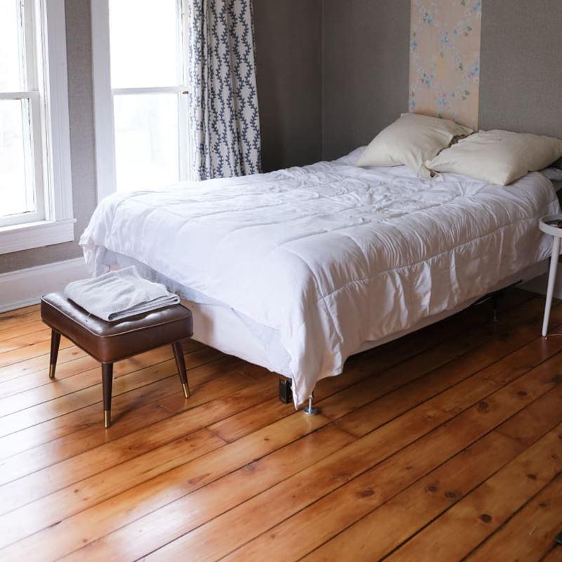 Декор маленькой спальни - кровать, деревянные полы и серые стены