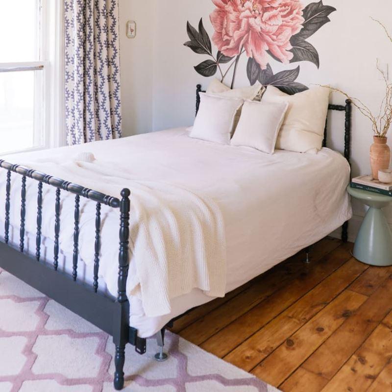 Декор маленькой спальни - ковер на полу, кровать с новым каркасом и наклейка с цветком у изголовья