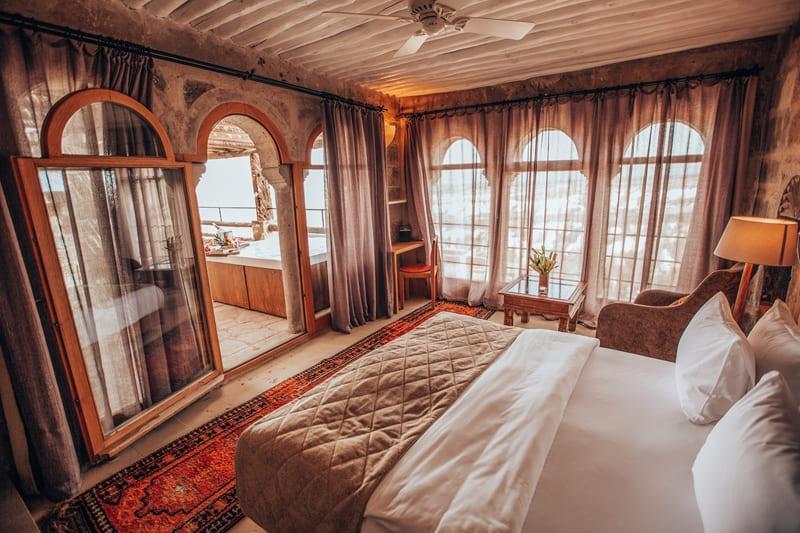 Отель Argos in Cappadocia (Турция) - номер Tiraz Jacuzzi Suite - спальня с террасой
