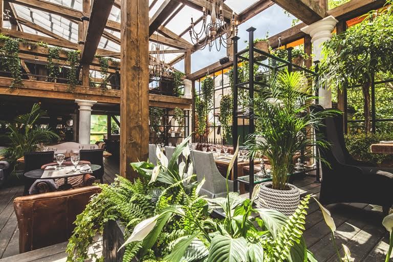 Летняя веранда ресторана Modus - деревянный интерьер с растениями