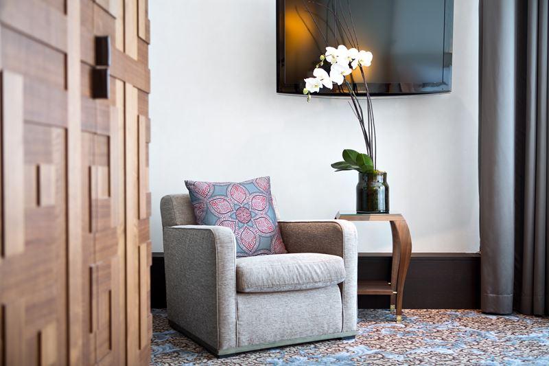The Ritz-Carlton Vienna - дизайн интерьера с мягким креслом и вазой с цветами