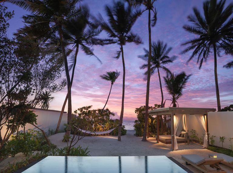 Курортный отель Fairmont Maldives Sirru Fen Fushi на Мальдивах - тропический закат с пальмами у бассейна