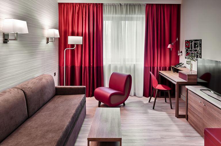 Adagio Москва Киевская - интерьер номера с диваном, креслом и шторами