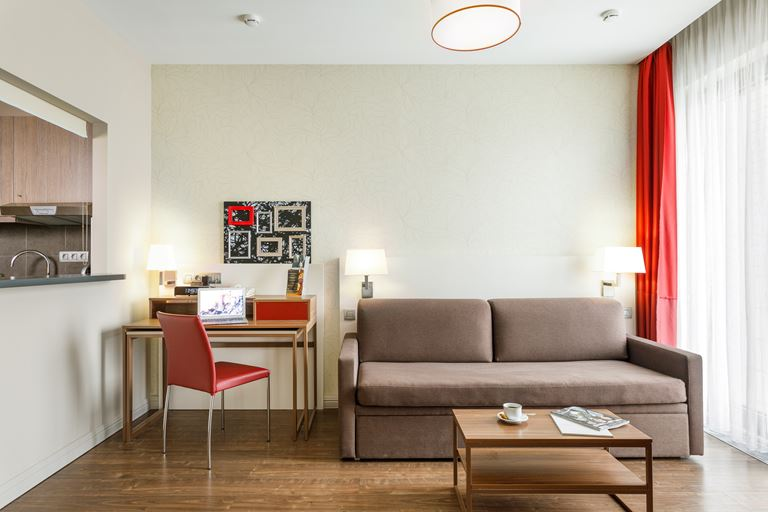 Апарт-отели Adagio – интерьер с бежевым диваном