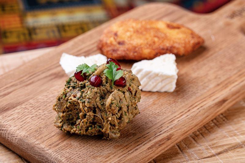 Иракли Дундуа, шеф-повар кафе домашней грузинской кухни Saperavi Cafe, предлагает свой рецепт пхали, основа которого – печёные баклажаны.   Ингредиенты: Баклажаны - 1 кг Фундук ядра - 70 г Грецкие орехи очищенные - 70 г Лук репчатый - 70 г Кинза - 50 г Чеснок - 10 г Уцхо сунели - пол чайной ложки Хмели кинза - пол чайной ложки Свежий перец чили - 2 г Красный чили молотой сухой - 2 г Соль - по вкусу  Процесс приготовления: Баклажаны помыть, обсушить.  Запекать в разогретой до 240 г духовке 20-30 мин (готовность проверять шпажкой). Запеченные баклажаны поместить в миску и накрыть пленкой. Дать остыть, затем снять кожицу, срезать плодоножки.  Отжать через марлю, мелко порубить ножом. Репчатый лук, чеснок, перец чили, орехи и зелень мелко порубить. Смешать с баклажанами. Добавить все специи кроме соли. Хорошо вымесить. Дать настояться час. Досолить, если потребуется. Сформировать шарики. Подавать по желанию с домашним сыром и мчади.