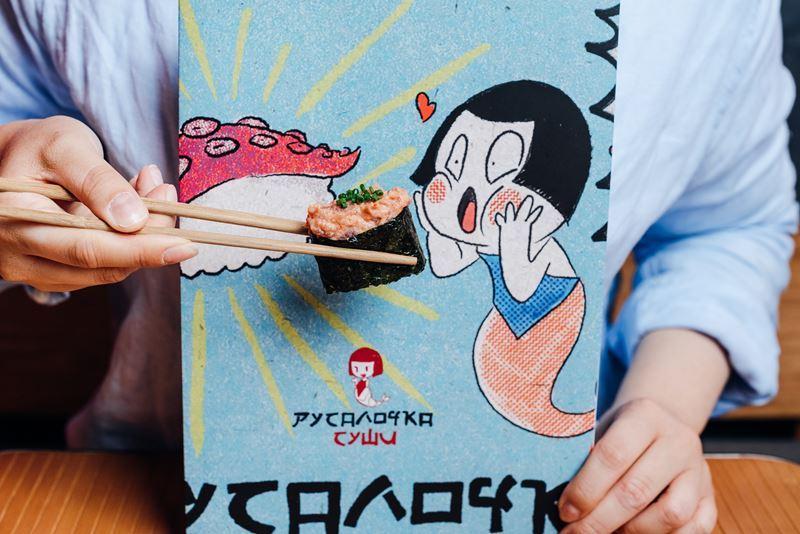 Проект маленькой Японской забегаловки – «Русалочка Суши» стартовал в июле 2019. За год работы он собрал множество поклонников, которых привлекает ироничная аутентичность концепции, в которой создана атмосфера городской закусочной, расположенной прямо на оживленной улице Нагоя или Токио, и звездные ребята, работающие в зале. В основе концепции неизменно лежит честный подход к продукту с правильным балансом цены и качества, что является главным фактором притяжения к дерзкой «Русалочке». В апреле 2020 года сушильня заработала в формате доставки, которая осуществляется в пределах МКАД.  «Благодаря, или даже, вопреки, короновирусу, нам пришлось усовершенствовать, передумать некоторые наши способы зарабатывания денег, и вообще подхода к ресторанам, - рассказывает Гоша Карпенко, соавтор концепции и генеральный директор HURMA Group of Companies. Мы, конечно, думали, что когда-то у нас будет доставка, но не сразу, но как только всех посадили по домам из-за пандемии, стало понятно, что спрос есть и надо оперативно запускаться. В результате оказалось, что если круто делать продукт, хорошо его упаковывать, и доставлять с помощью классного курьера, который несет с собой часть сути концепции, люди с радостью его заказывают».  Следующий шаг развития концепции – переход в формат дарк китчен на районе. По сути, это ресторан без ресторана. Первой локацией для «Русалочки» онлайн становится район Крылатское. Открытие этой точки состоялось 3 августа.  «Посчитав, что для открытия в новом районе нужно привести людей в офлайн, чтобы они потом уже перешли в доставку, мы решили миновать пункт с офлайн-местом и сразу же прийти в точку «В». За год мы планируем открыть десять дарк китчен в разных районах. Мы сокращаем диаметр до 3 км, чтобы укладываться с доставкой в 15 – 20 минут. Для нас преимущества дарк китчен это – другая аренда, иные условия по помещению, минимальная цена запуска и цена ошибки значительно меньше. Если откроем локацию и она не пойдет, мы без особых потерь переедем в другой